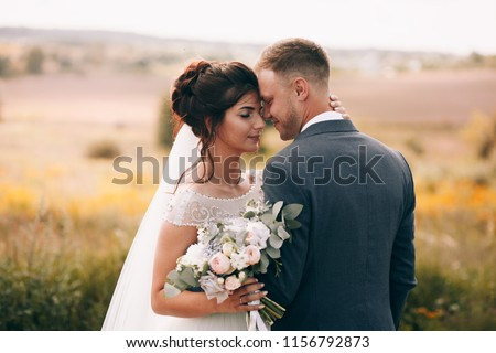 Bride and groom in a park kissing.couple newlyweds bride and groom at a wedding in nature green forest are kissing photo portrait.Wedding Couple #1156792873
