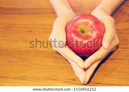 Hand holding red apple on wood table background, love yourself concept, healthy medical, you are what you eat concept,fruits, healthcare #1156856212