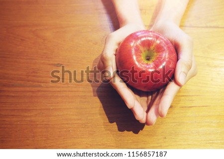 Hand holding red apple on wood table background, love yourself concept, healthy medical, you are what you eat concept,fruits, healthcare #1156857187