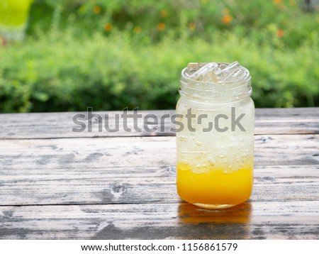 A fresh orange soda drink filled with ice in a vintage style glass container Full of ice in the glass. Placed on a wooden desk in garden with a green background #1156861579