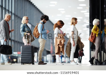Side view of multiracial people standing in queue to check in in airport hall #1156919401