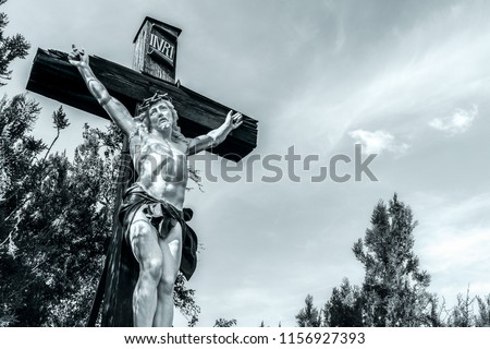 Black and white or monochrome picture of a big crucifix of Jesus-Christ with copy space, outdoor, Alsace, France.