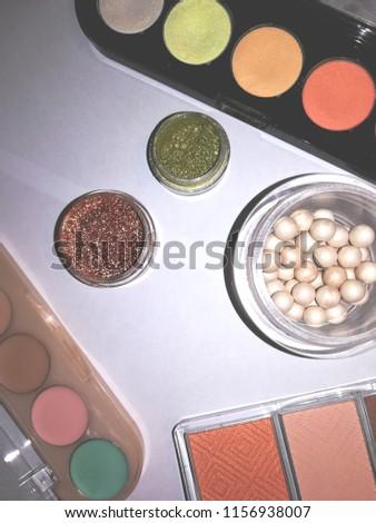 Cosmetics: powder, colorful eyeshadows, blusher at the light background #1156938007
