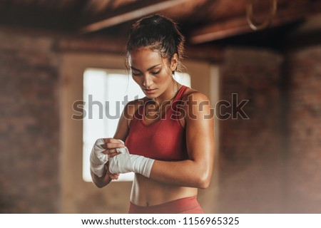 Female boxer wearing strap on wrist. Fitness young woman with muscular body preparing for boxing training at gym. #1156965325