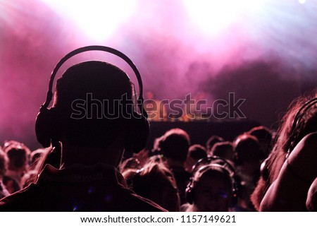 A man wearing a pair of headphones enjoying a silent disco. Royalty-Free Stock Photo #1157149621