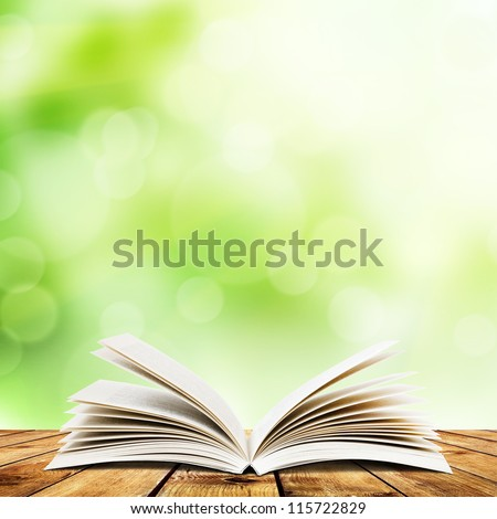 Open book on wood planks over abstract light background #115722829