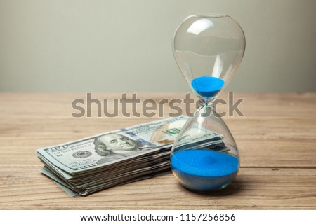 Hourglass and stack of money dollars of banknotes. Time is money #1157256856
