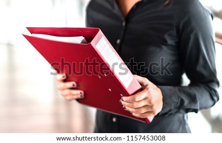 Professional business woman holding folder full of paper documents. Lawyer, legal adviser, office assistant or company manager with binder. Royalty-Free Stock Photo #1157453008