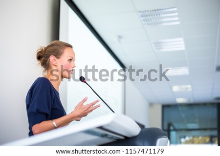 Pretty, young business woman giving a presentation in a conference/meeting setting (shallow DOF; color toned image) #1157471179