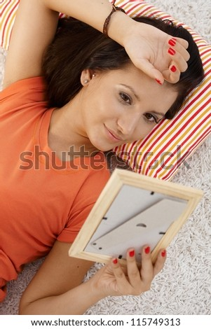 Young woman in love, looking at photo of boyfriend, daydreaming at home. #115749313