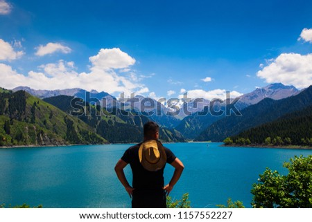 Back side rear view of man look at great view landscape of Lake Mountain Blue Sky in lovely summer vacation holiday during travel hiking on final destination
