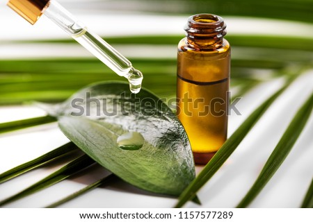 essential oil dripping on the green leaf from pipette #1157577289