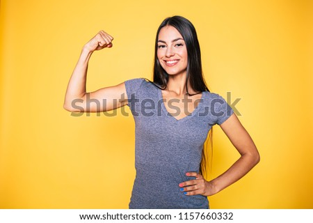 Sport, healthy lifestyle, gym, good body condition, women health, fitness concepts. Close up Portrait of Young cute sporty smiling brunette woman while she shows her arms and biceps on camera Royalty-Free Stock Photo #1157660332