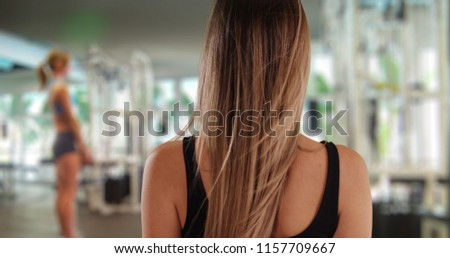 Rear view of athletic woman after exercising in gym setting #1157709667