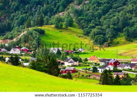 Norwegian fjord village landscape near Flam, Norway. Green hill meadows with houses #1157725354