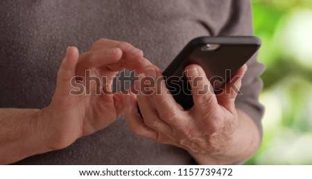 Tight shot of senior person's hands holding cell phone texting in nature setting #1157739472