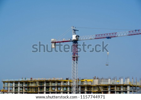 Construction of multi storey residential complex tower cranes in operation. as a rule, equipped with lifting ropes ropes or chains and bundles which can be used both for lifting and lowering materials #1157744971