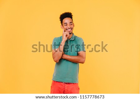 Handsome african man thinking about something with smile. Indoor shot of positive black guy expressing good emotions on bright background.