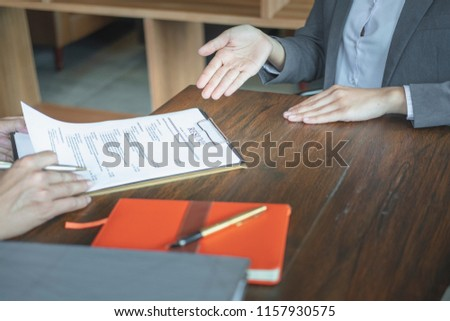 Woman submits job application, Interviewer reading a resume. #1157930575