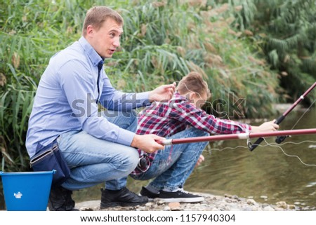 Excited adult man fishing on freshwater lake from shore on forest #1157940304