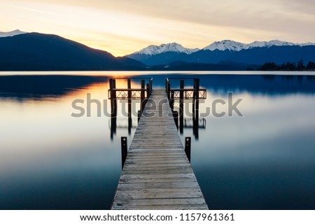 Sunset from a wharf in the lake of Te Anau, New Zealand #1157961361