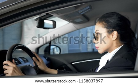 Confident female in business suit sitting in car national security agent on duty Royalty-Free Stock Photo #1158037897