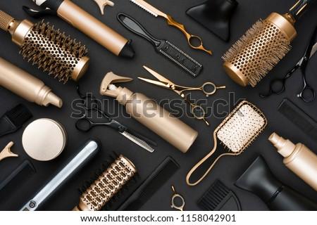 Full frame of professional hair dresser tools on black background