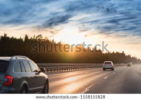 Highway traffic in sunset. Road with metal safety barrier or rail. cars on the asphalt under the cloudy sky. #1158115828