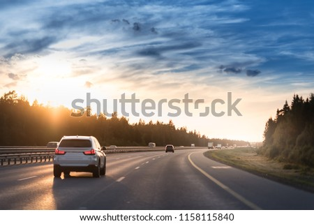 Highway traffic in sunset. Road with metal safety barrier or rail. cars on the asphalt under the cloudy sky. #1158115840
