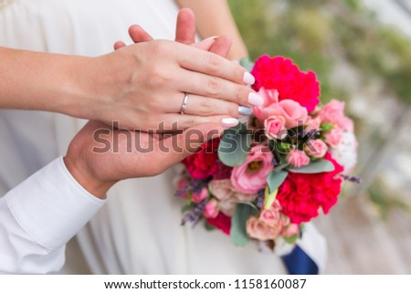 Couples hands wearing their wedding rings resting on the wedding bouqet #1158160087