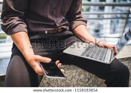 Close up handsome young male hands hold mobile phone and laptop computer , Technology communication concept #1158183856