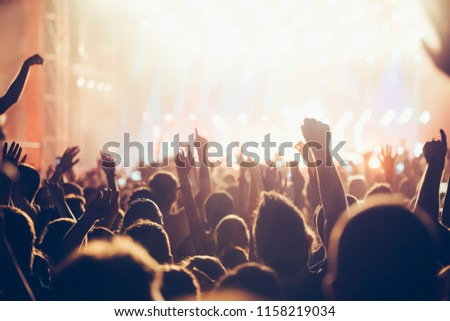 Cheering crowd with hands in air at music festival #1158219034