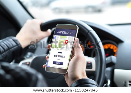 Ride share driver in car using the rideshare app in mobile phone. New taxi ride request from customer in smartphone application. Man picking up passengers for online carpool service. #1158247045