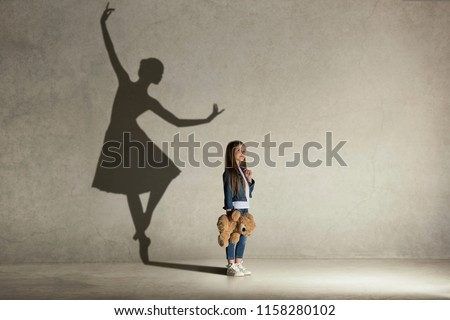 Baby girl dreaming about dancing ballet. Childhood and dream concept. Conceptual image with shadow of ballerina on the studio wall #1158280102