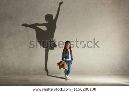 Baby girl dreaming about dancing ballet. Childhood and dream concept. Conceptual image with shadow of ballerina on the studio wall #1158280108