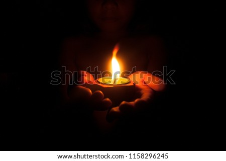 Little child holding burning candle in darkness with noise and grain effect. Royalty-Free Stock Photo #1158296245