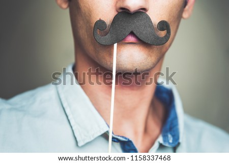 close up of a man's chin wearing a fake paper made mustache #1158337468