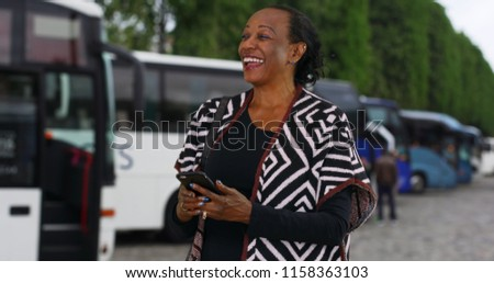 Happy elderly black woman using her cellphone looking away camera near buses #1158363103