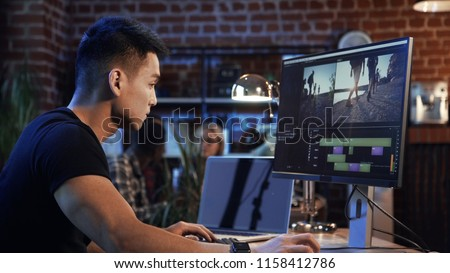 Side view of casual confident Korean man working on computer with video editing and color correction Royalty-Free Stock Photo #1158412786