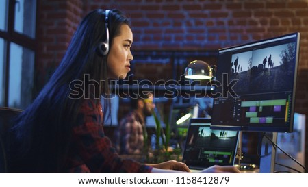 Side view of casual Korean girl wearing headphones and editing video in office working at table