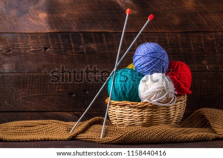 Color thread for knitting, knitted scarf, knitting needles on a dark background. Copy space. Knitting concept #1158440416