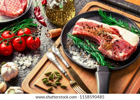 Raw meat on the kitchen table on a metallic background in a composition with cooking accessories #1158590485