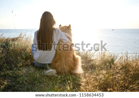 young beautiful woman with long hair walking with collie dog. Outdoors in the park. near the sea, summer beatch #1158634453