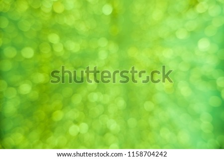Abstract green bokeh circles for Christmas background. Royalty high-quality free stock photo of Christmas light overlay background. Holiday glowing backdrop. Defocused background with blinking stars