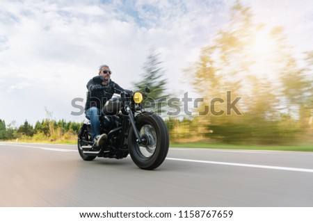 High power motorcycle chopper on the country road riding. having fun driving the empty road on a motorcycle tour #1158767659