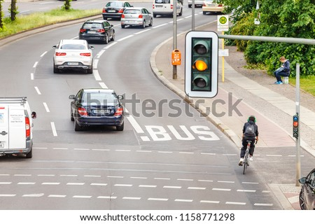 16 MAY 2018, BERLIN, GERMANY: Aerial view of Traffic light above busy road in the city with cyclist, cars and public trasport lane. Road safety concept #1158771298