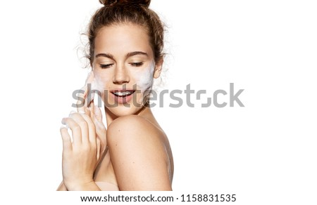 Portrait of girl touching flawless soft skin on white background. Woman using foam for wetting face. Pampering and freshness concept.  #1158831535