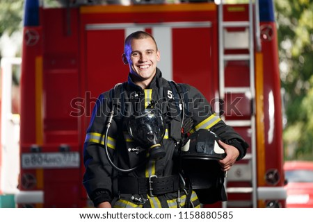 Photo of happy fireman with gas mask and helmet near fire engine #1158880585