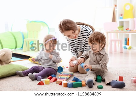 Young nanny playing with little children, indoors #1158884899