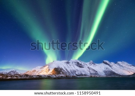Aurora borealis on the Lofoten islands, Norway. Green northern lights above mountains. Night sky with polar lights. Night winter landscape with aurora and reflection on the water surface.  #1158950491
